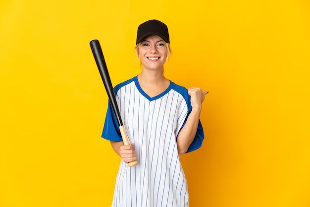 Jeune femme russe isolée sur jaune jouant au baseball et pointant vers le côté pour présenter un produit