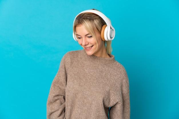 Jeune femme russe isolée sur un mur bleu à l'écoute de la musique