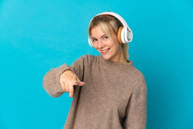 Jeune femme russe isolée sur la musique d'écoute bleue
