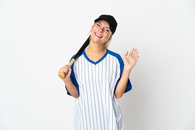 Jeune femme russe jouant au baseball isolé sur fond blanc saluant avec la main avec une expression heureuse