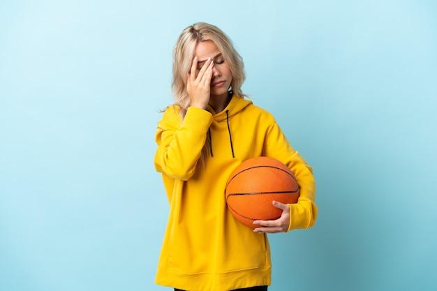 Jeune femme russe jouant au basket isolé sur bleu avec des maux de tête