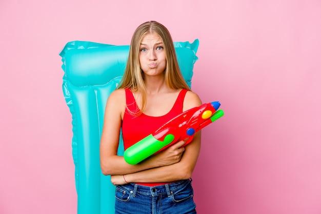 Jeune femme russe jouant avec un pistolet à eau avec un matelas pneumatique souffle sur les joues, a une expression fatiguée. concept d'expression faciale.