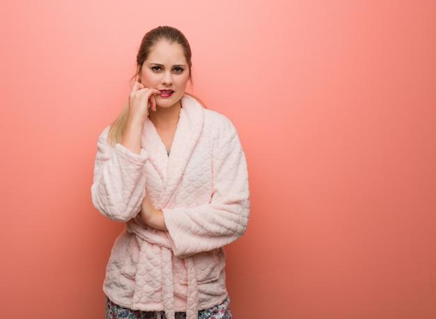 Jeune femme russe en pyjama se ronger les ongles, nerveuse et très anxieuse