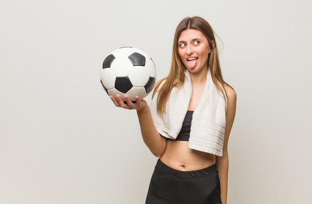 Jeune femme russe de remise en forme drôle et sympathique montrant la langue. tenant un ballon de soccer.