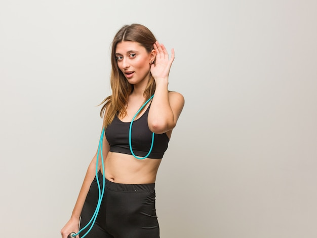 Jeune femme russe de remise en forme essaie d'écouter des potins. tenant une corde à sauter.