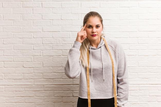Jeune femme russe de remise en forme tenant un ruban de mesure