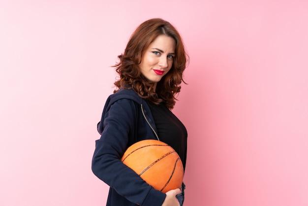 Jeune femme russe sur rose isolé avec ballon de basket