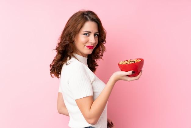 Jeune femme russe sur rose isolé tenant un bol de céréales