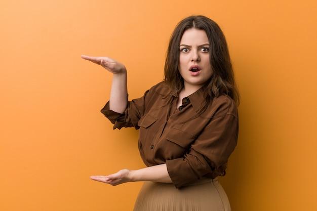 Jeune femme russe sinueuse choquée et émerveillée tenant un espace de copie entre les mains.
