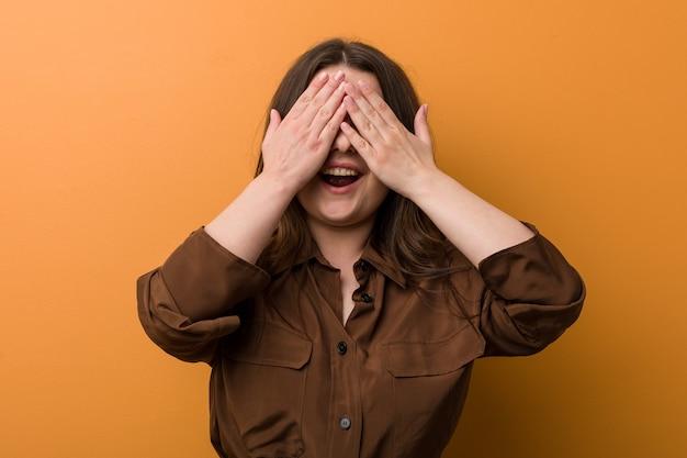 Jeune femme russe sinueuse couvre les yeux avec les mains, sourit largement en attendant une surprise.