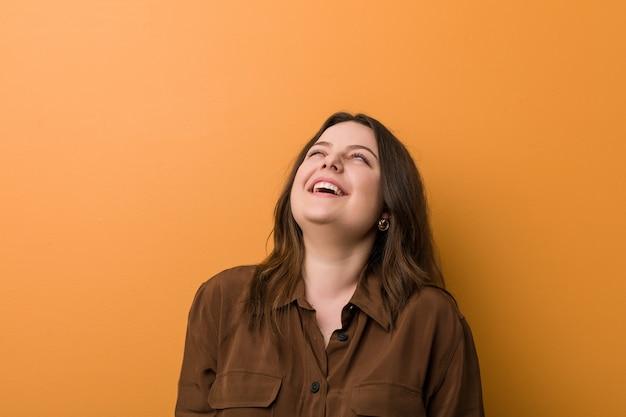 Jeune femme russe sinueuse détendue et heureuse en riant, cou tendu montrant les dents.