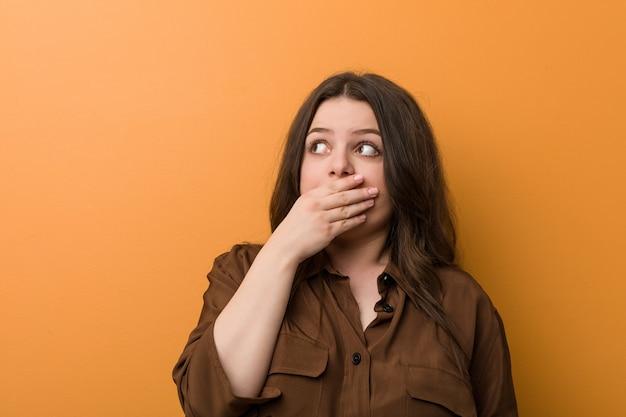 Jeune femme russe sinueuse réfléchie à la recherche d'un espace de copie couvrant la bouche avec la main.