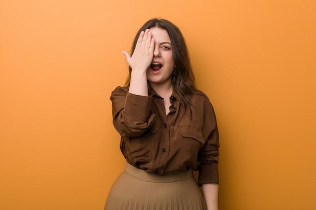 Jeune femme russe sinueuse s'amusant couvrant la moitié du visage avec la paume.
