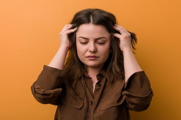 Jeune femme russe sinueuse, touchant les temples et ayant mal à la tête.