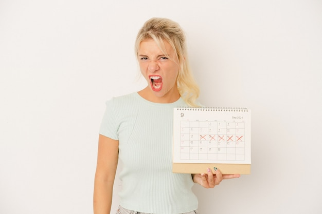 Jeune femme russe tenant un calendrier isolé sur fond blanc criant très en colère et agressif.
