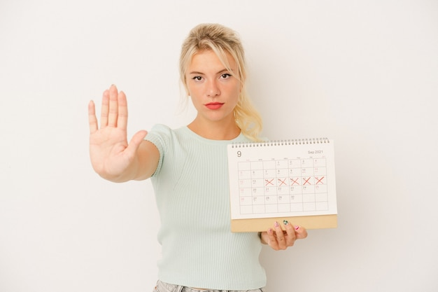 Jeune femme russe tenant un calendrier isolé sur fond blanc debout avec la main tendue montrant un panneau d'arrêt, vous empêchant.