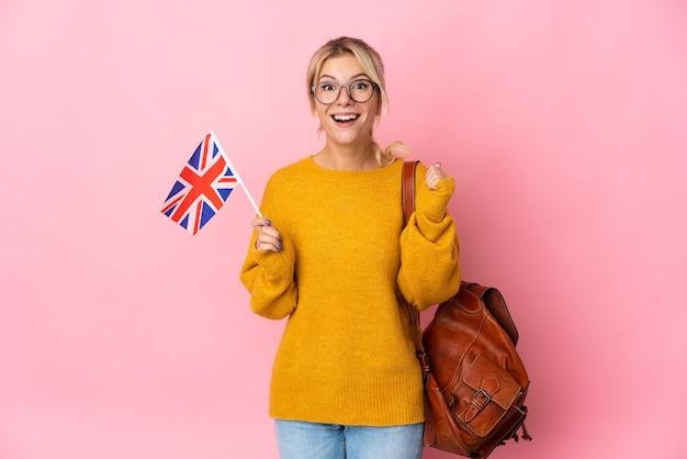 Jeune femme russe tenant un drapeau du royaume-uni isolé sur fond rose célébrant une victoire en position de vainqueur