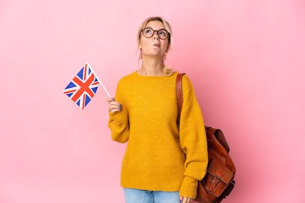 Jeune femme russe tenant un drapeau du royaume-uni isolé sur fond rose et levant