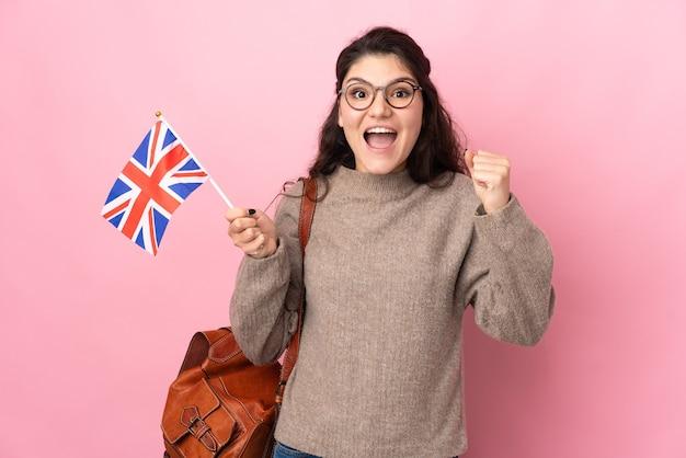 Jeune femme russe tenant un drapeau du royaume-uni isolé sur un mur rose célébrant une victoire en position de vainqueur