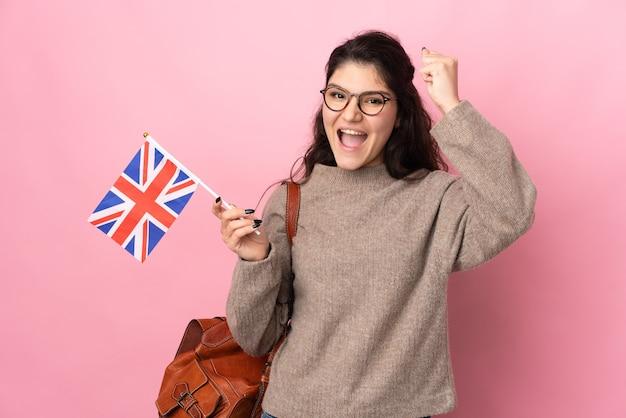 Jeune femme russe tenant un drapeau du royaume-uni isolé sur un mur rose célébrant une victoire