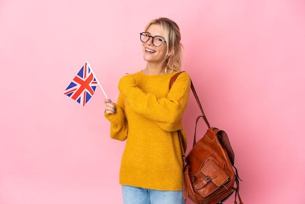 Jeune femme russe tenant un drapeau du royaume-uni isolé sur rose célébrant une victoire