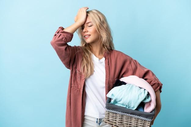 Jeune femme russe tenant un panier de vêtements isolé sur bleu a réalisé quelque chose et l'intention de la solution