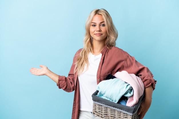 Jeune femme russe tenant un panier de vêtements isolé sur fond bleu étendant les mains sur le côté pour inviter à venir