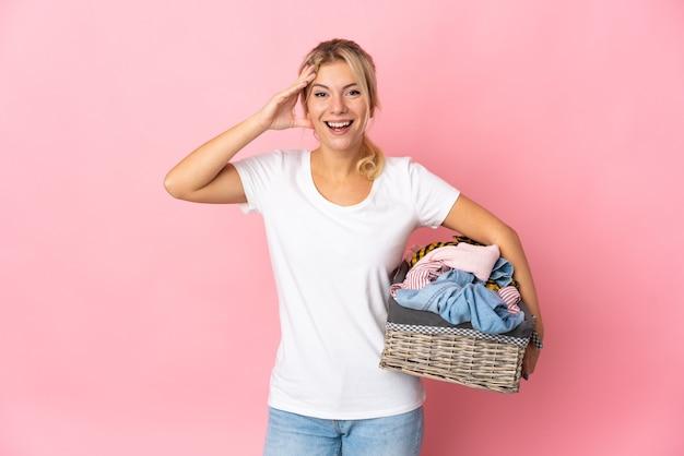 Jeune femme russe tenant un panier de vêtements isolé sur fond rose avec une expression de surprise