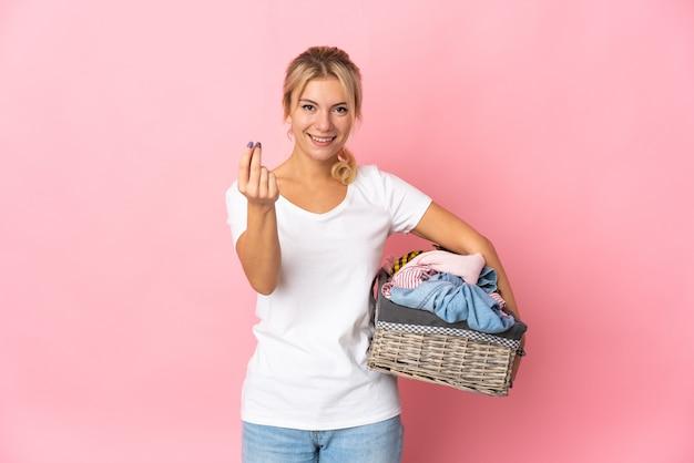 Jeune femme russe tenant un panier de vêtements isolé sur fond rose faisant le geste de l'argent