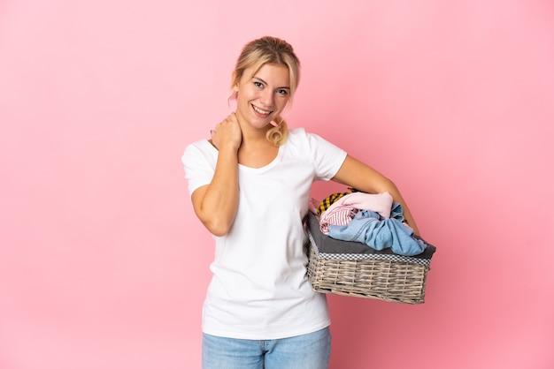 Jeune femme russe tenant un panier de vêtements isolé sur fond rose en riant