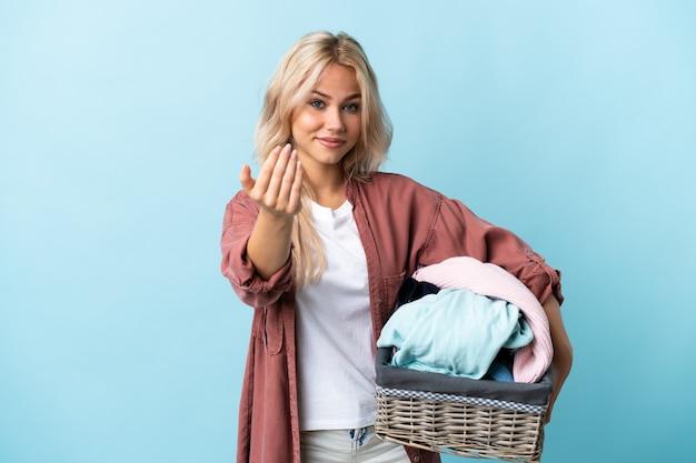 Jeune femme russe tenant un panier de vêtements isolé sur mur bleu invitant à venir avec la main. heureux que tu sois venu