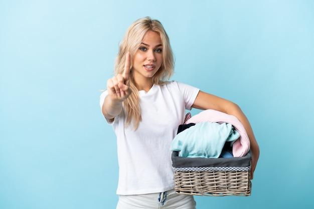 Jeune femme russe tenant un panier de vêtements isolé sur un mur bleu montrant et en soulevant un doigt