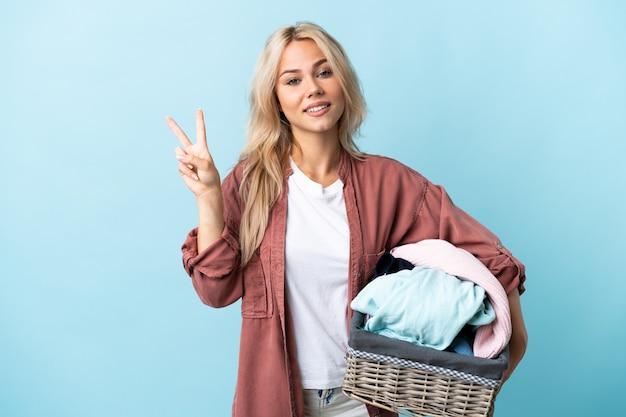 Jeune femme russe tenant un panier de vêtements isolé sur mur bleu souriant et montrant le signe de la victoire