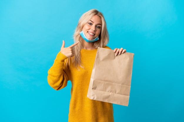 Jeune femme russe tenant un sac d'épicerie isolé sur bleu donnant un geste de pouce en l'air