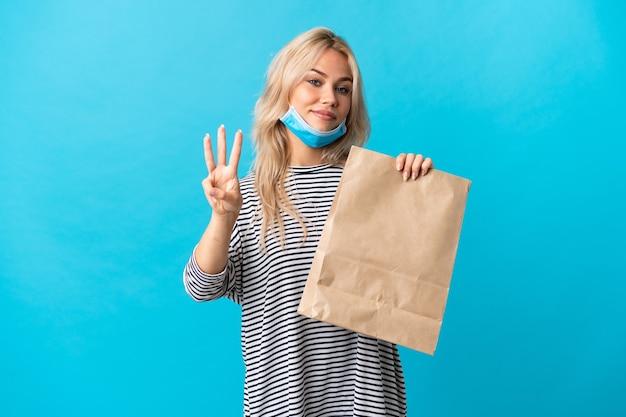 Jeune femme russe tenant un sac d'épicerie isolé sur bleu heureux et en comptant trois avec les doigts