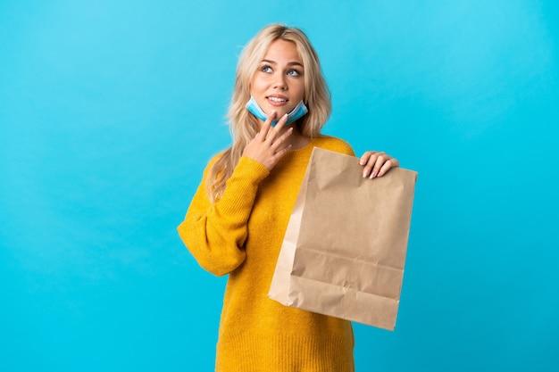 Jeune femme russe tenant un sac d'épicerie isolé sur bleu en regardant en souriant