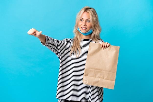 Jeune femme russe tenant un sac d'épicerie isolé sur fond bleu donnant un geste de pouce en l'air