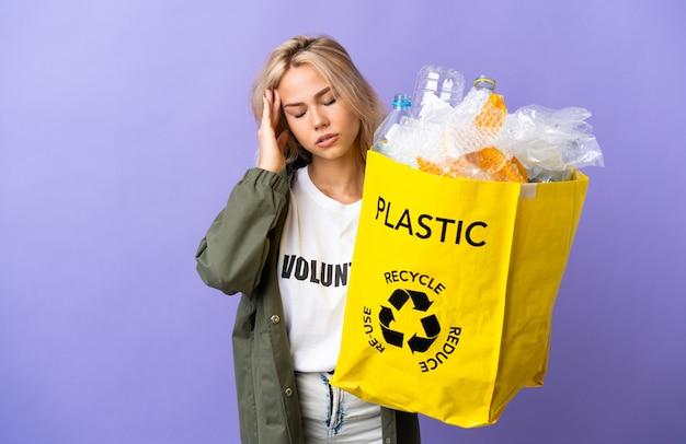 Jeune femme russe tenant un sac de recyclage plein de papier à recycler isolé sur mur violet avec maux de tête