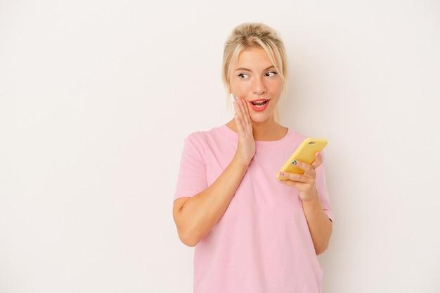 Jeune femme russe tenant un téléphone portable isolé sur fond blanc dit une nouvelle secrète de freinage à chaud et regarde de côté