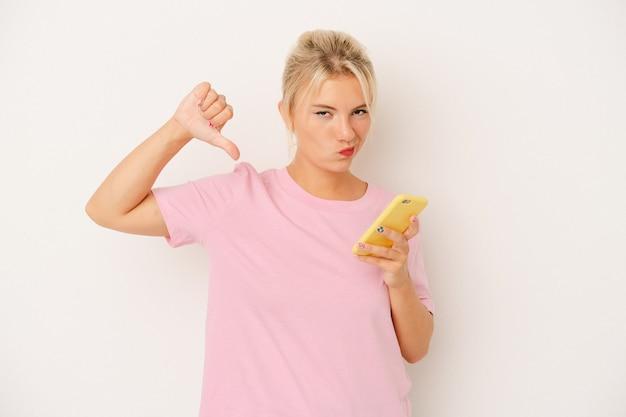 Jeune femme russe tenant un téléphone portable isolé sur fond blanc se sent fière et confiante, exemple à suivre.