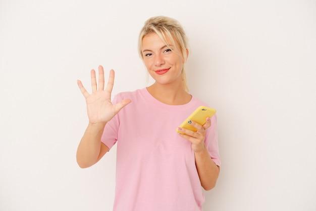 Jeune femme russe tenant un téléphone portable isolé sur fond blanc souriant joyeux montrant le numéro cinq avec les doigts.