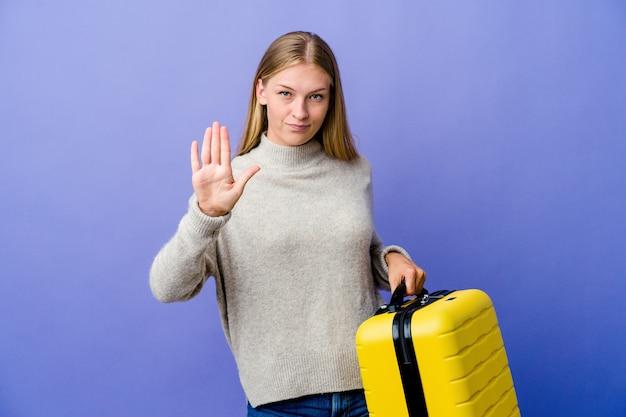 Jeune femme russe tenant une valise pour voyager montrant un geste de temporisation.