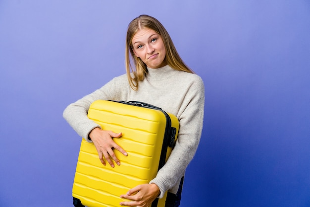 Jeune femme russe tenant une valise pour voyager qui se sent en confiance, croisant les bras avec détermination.