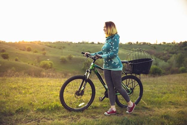 Jeune femme s'amusant près du parc de campagne faisant du vélo voyageant au printemps