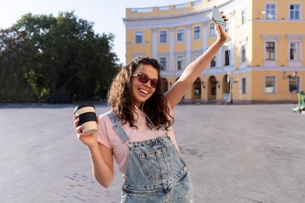 Jeune femme s'amusant tout en tenant une tasse de café