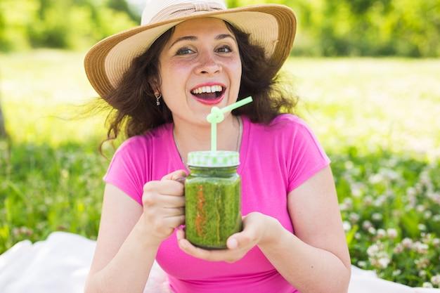 Une jeune femme s'amuse dans le parc et boit des smoothies verts lors d'un pique-nique.