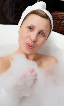 Jeune femme s'amuser dans un bain moussant