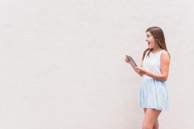 Jeune femme s'amuser avec une tablette sur fond blanc