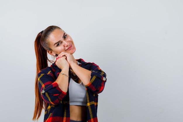 Jeune femme s'appuyant sur les mains jointes en haut, chemise à carreaux et l'air paisible, vue de face.