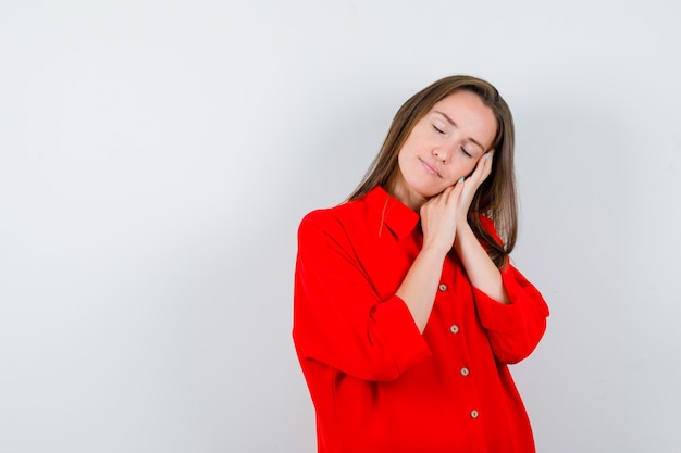 Jeune femme s'appuyant sur les paumes comme oreiller en chemisier rouge et semblant paisible, vue de face.
